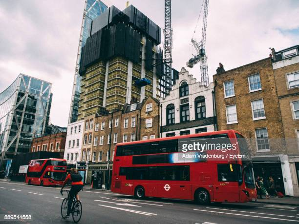 double-decker bus on road against sky in city - double decker bus stock pictures, royalty-free photos & images