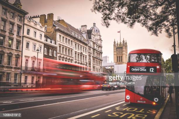 double-decker bus on road in city during sunset - double decker bus stock pictures, royalty-free photos & images