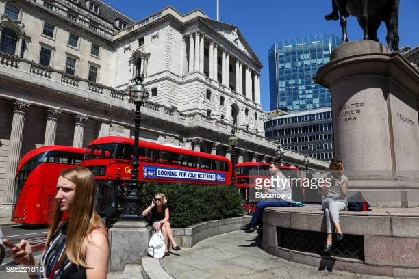 Doubledecker red buses including one with an advertisement reading 'Looking for your next job' pass the Bank of England in the City of London UK on...