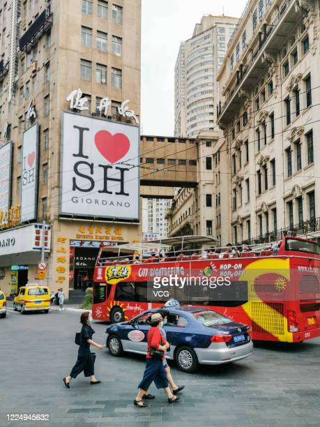 """Double-decker tour bus runs under a billboard reading """"I Love SH """" around Nanjing Road pedestrian street on May 14, 2020 in Shanghai, China."""