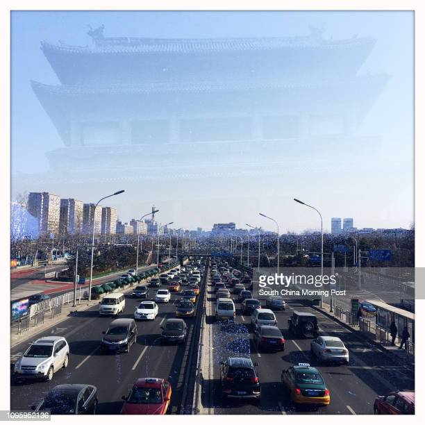 Double-exposure photo taken with an app on iPhone shows the demolished Andingmen Gate Tower and Beijing's Second Ring Road at Andingmen flyover,...