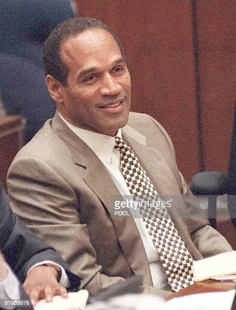Doublemurder defendant OJ Simpson smiles as his daughter Arnelle Simpson takes the witness stand while the defense started its case 10 July in the OJ...