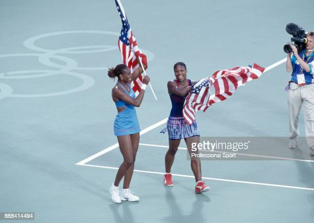 Doubles partners and sisters Venus Williams and Serena Williams of the USA celebrate with their flags after defeating Kristie Boogert and Miriam...