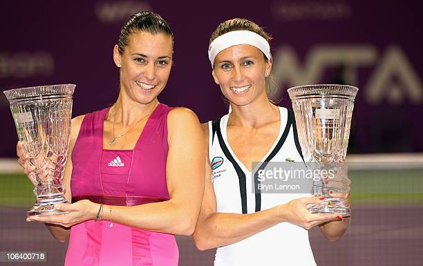 Doubles partners Flavia Pennetta of Italy and Gisela Dulko of Argentina pose with their trophies after winning the doubles final on day six of the...