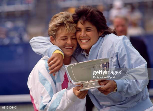 Doubles partners Gigi Fernandez and Robin White both of the USA celebrate with the trophy after defeating Patty Fendick of the USA and Jill...
