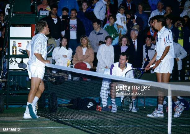 Doubles partners John McEnroe of the USA and Michael Stich of Germany and their opponent Richey Reneberg of the USA discuss the playing conditions...