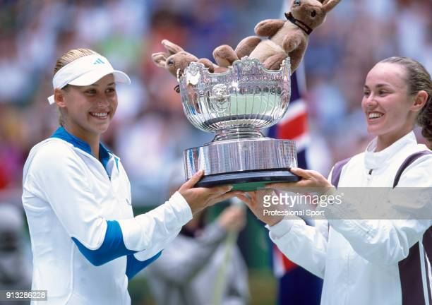 Doubles partners Martina Hingis of Switzerland and Anna Kournikova of Russia lift the trophy after defeating Daniela Hantuchova of Slovakia and...