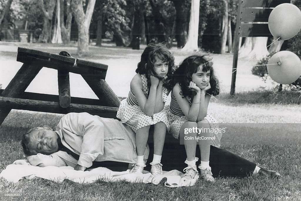 Doubling up on grandpa; While Frank Spensieri takes advantage of the warm summer weather for a snooze; his twin granddaughters Cara; left; and Lori Spensieri take time out for a rest.