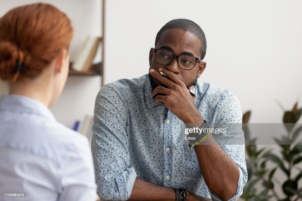 Doubtful african hr talking to caucasian applicant at job interview : Stock Photo
