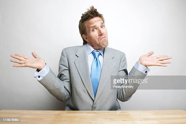 Doubtful Confused Office Worker Businessman Shrugs Shoulders at his Desk