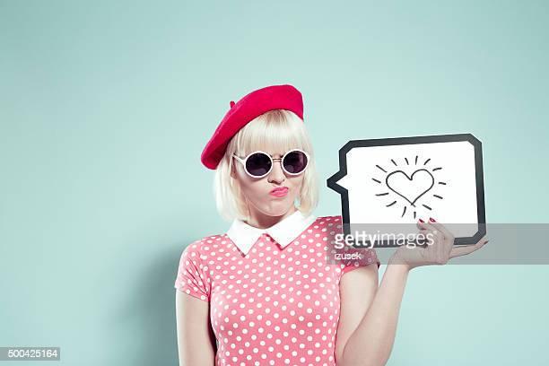 Doubtfully joven mujer agarrando discurso burbujas con extracción de corazón