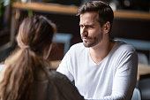 Doubting dissatisfied man looking at woman, bad first date concept
