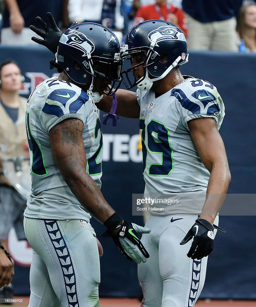 Doug Baldwin #89 and Marshawn Lynch #24 of the Seattle Seahawks celebrate after Lynch scored a fourth quarter touchdown against the Houston Texans at Reliant Stadium on September 29, 2013 in Houston, Texas.