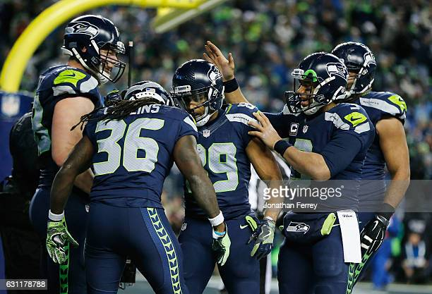 Doug Baldwin and Russell Wilson of the Seattle Seahawks celebrate with teammates after scoring a 13yard touchdown during the fourth quarter against...