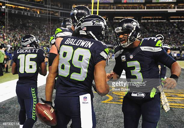 Doug Baldwin celebrates with Russell Wilson of the Seattle Seahawks in the end zone after scoring a touchdown during the third quarter against the...