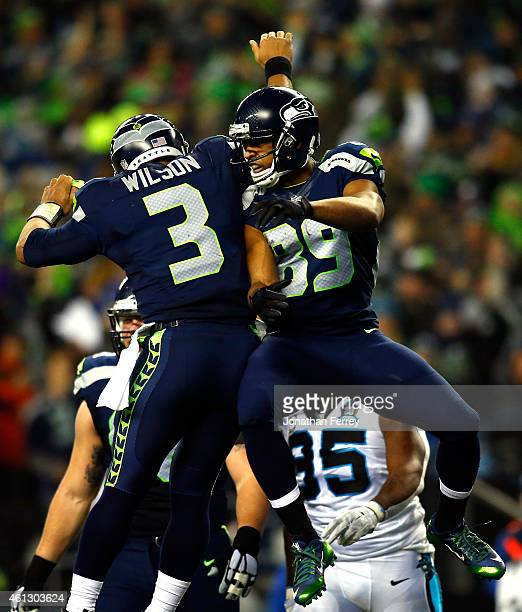 Doug Baldwin of the Seattle Seahawks celebrates with Russell Wilson after catching a 16 yard touchdown pass in the first quarter against the Carolina...