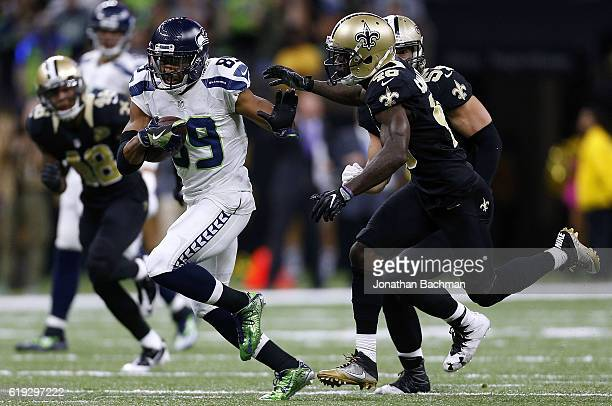 Doug Baldwin of the Seattle Seahawks runs with the ball as Ken Crawley of the New Orleans Saints defends during the second half of a game at the...