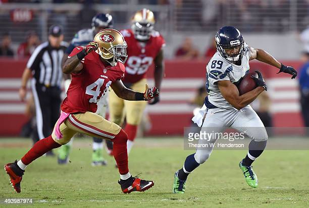 Doug Baldwin of the Seattle Seahawks runs with the ball while pursued by Antoine Bethea of the San Francisco 49ers during an NFL football game at...