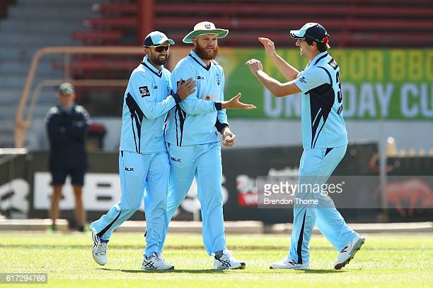 Doug Bollinger of the Blues celebrates with team mates Nathan Lyon and Patrick Cummins after catching out Nathan Reardon of the Bulls during the...