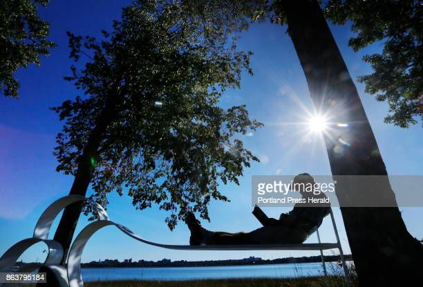 Doug Brown of Portland reads a book while relaxing on Cloud Cloud a steel bench scupture created by Vivian Beer in 2008 along Back Cove in Portland...