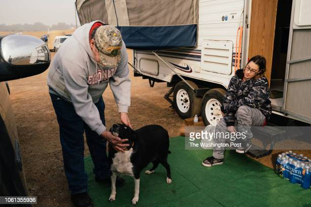 Doug Chandler pets his dog KC as his girlfriend Jackie Humphreys waits for word on their homes condition at the Church of the Nazarene in Oroville...