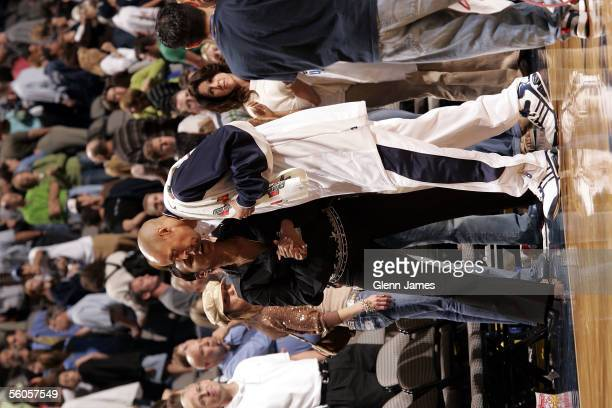 Doug Christie of the Dallas Mavericks talks with his wife Jackie before the preseason game against the New York Knicks at American Airlines Arena on...
