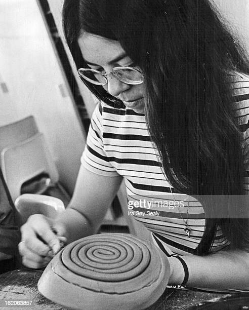 Doug Cole, left, uses potters wheel to tool a design on pot. Above, Marilyn Alvarez uses another form of pottery creation as she builds a clay bowl...