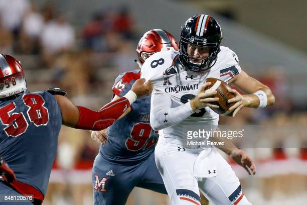 Doug Costin and Pasquale Calcagno of the Miami Ohio Redhawks sacks Hayden Moore of the Cincinnati Bearcats during the first half at Yager Stadium on...