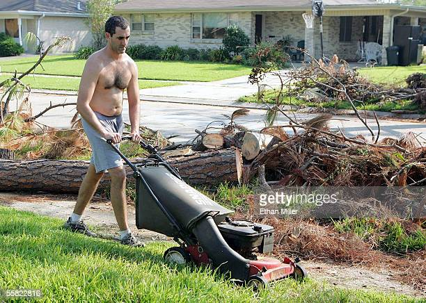 Doug Curole mows his lawn in front of trees knocked down by Hurricane Katrina in the Algiers District September 28 2005 in New Orleans Louisiana...
