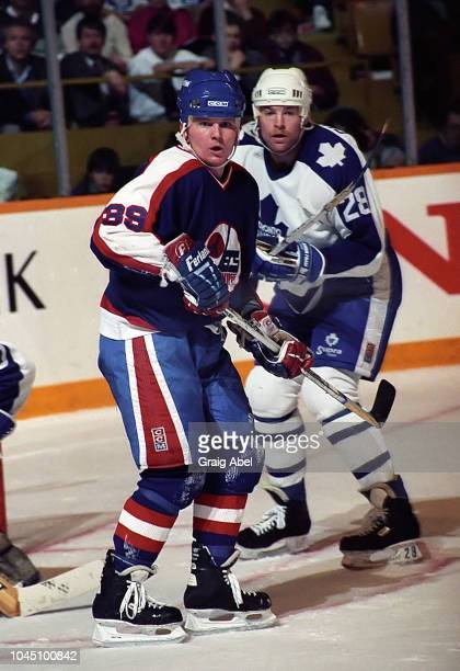 Doug Evans of the Winnipeg Jets skates against Brian Curran of the Toronto Maple Leafs during NHL game action on March 17 1990 at Air Canada Centre...