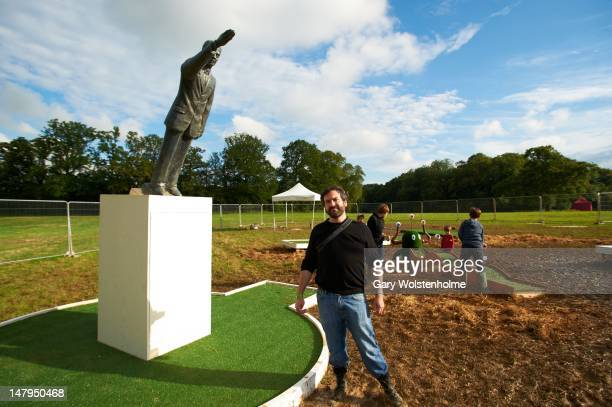 Doug Fishbone poses with his adventure golf sculpture of Saddam Hussien falling during Nova Festival of Arts Music at Bignor Park on July 6 2012 in...