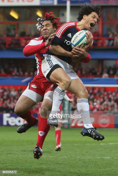Doug Howlett of Munster is wrapped up by Lesley Vainikolo of Gloucester as he claims a high ball during the Heineken Cup quarter final match between...