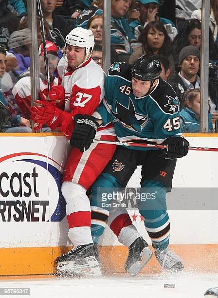 Doug Janik of the Detroit Red Wings is hit by Jody Shelley of the San Jose Sharks during an NHL game on January 9, 2010 at HP Pavilion at San Jose in...