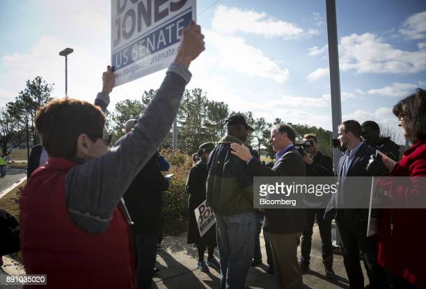 Doug Jones Democratic US Senate candidate from Alabama center right shakes hands with a voter outside a polling location in Bessemer Alabama US on...