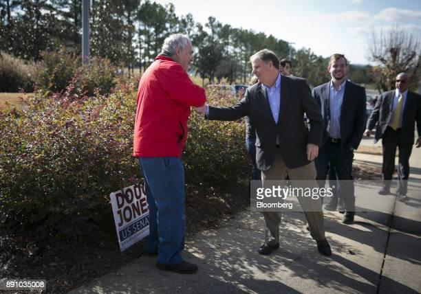 Doug Jones Democratic US Senate candidate from Alabama center shakes hands with a voter outside a polling location in Bessemer Alabama US on Tuesday...