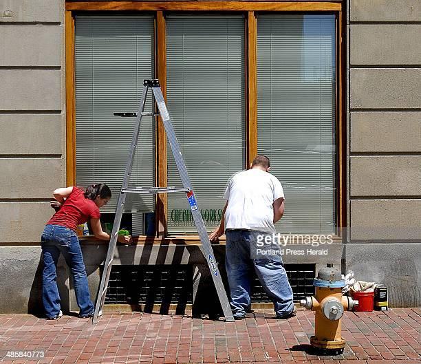 Doug Jones/Staff Photographer Brittney Cuomo and Taylor Jerome of Christine's LLC refinish the Elm Street windows of a building at the corner of Elm...