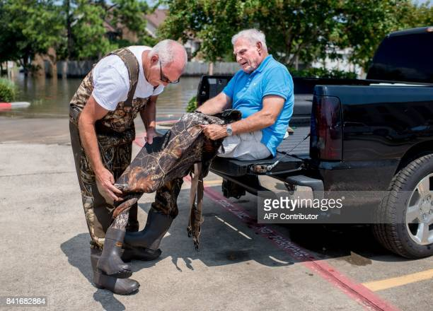 Doug Leblanc helps his father John Leblanc put on waders to go clean out the fridge in John's flooded home in Port Arthur Texas on Thursday September...