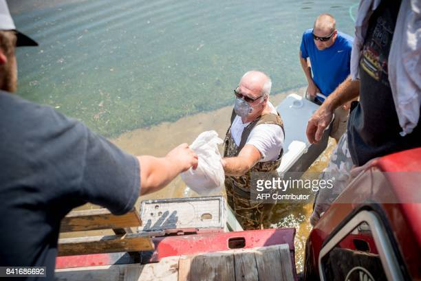 Doug Leblanc passes up bread to a rescue team in Port Arthur Texas on Thursday September 1 2017 Stormweary residents of Houston and other Texas...