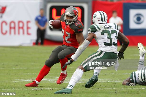 Doug Martin of the Bucs carries the ball as Jamal Adams of the Jets closes in during the regular season game between the New York Jets and the Tampa...