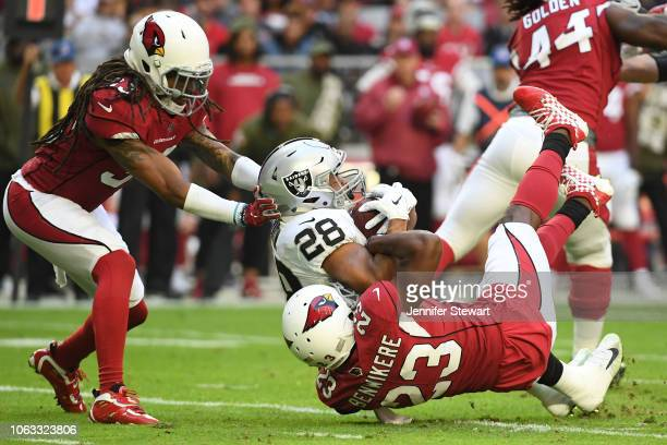 Doug Martin of the Oakland Raiders is tackled by Bene' Benwikere of the Arizona Cardinals in the first half at State Farm Stadium on November 18 2018...