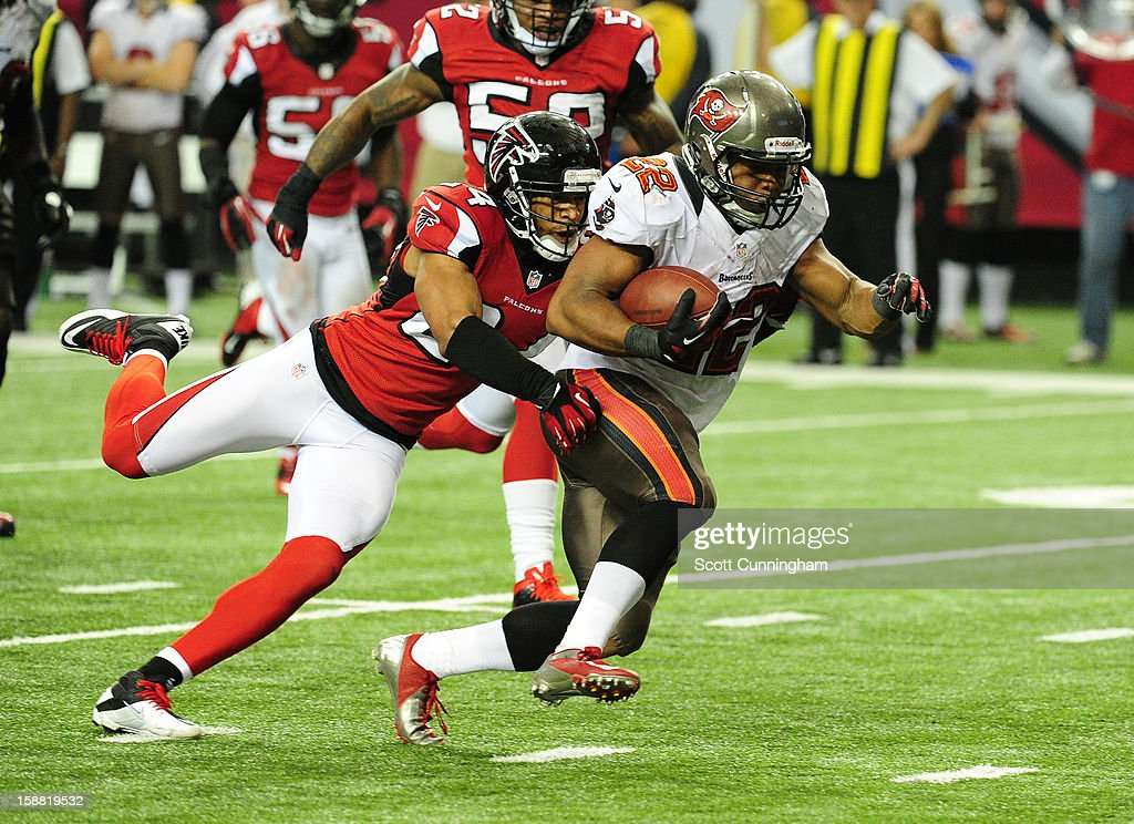 Doug Martin #22 of the Tampa Bay Buccaneers carries the ball against Chris Hope #24 of the Atlanta Falcons at the Georgia Dome on December 30, 2012 in Atlanta, Georgia