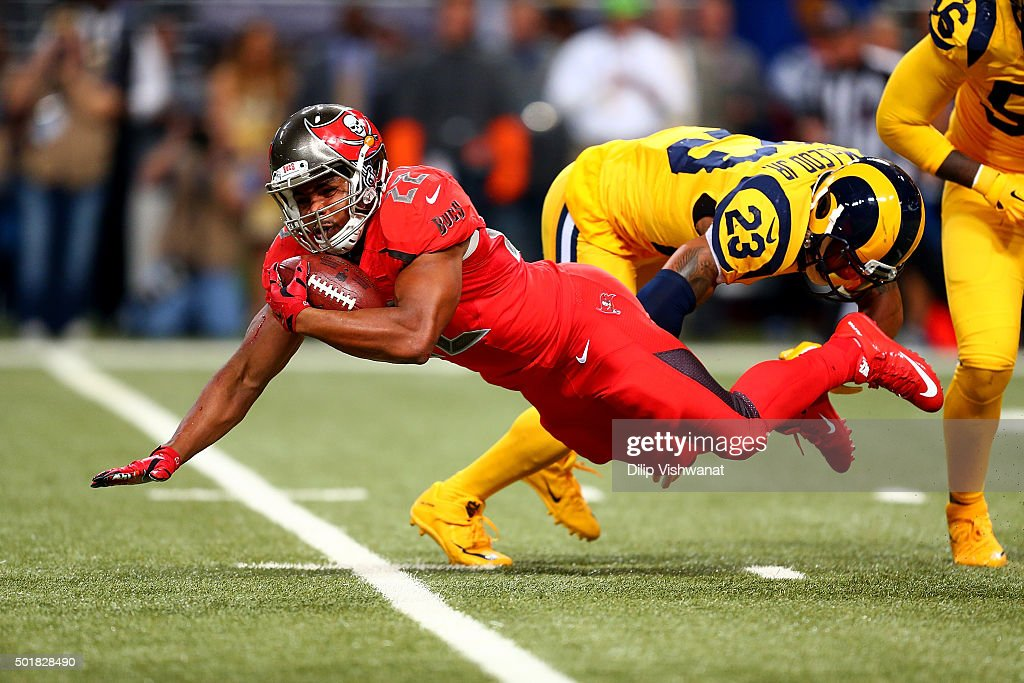 Doug Martin #22 of the Tampa Bay Buccaneers goes down after a hit from Rodney McLeod #23 of the St. Louis Rams in the second quarter at the Edward Jones Dome on December 17, 2015 in St. Louis, Missouri.