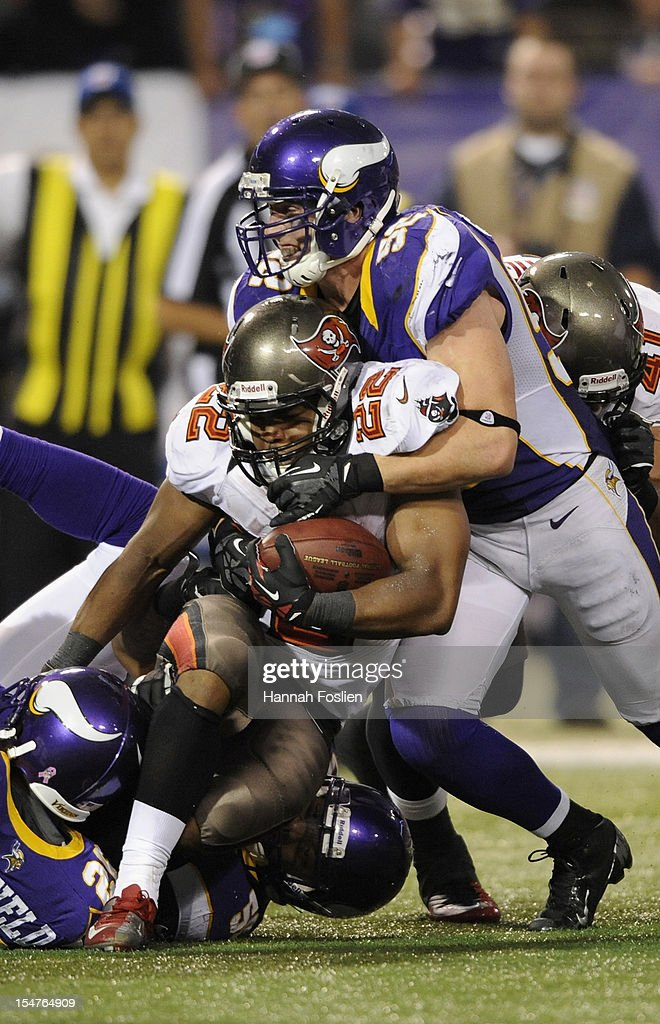 Doug Martin #22 of the Tampa Bay Buccaneers is tackled by Antoine Winfield #26 and Chad Greenway #52 of the Minnesota Vikings during the fourth quarter of the game on October 25, 2012 at Mall of America Field at the Hubert H. Humphrey Metrodome in Minneapolis, Minnesota. The Buccaneers defeated the Vikings 36-17.