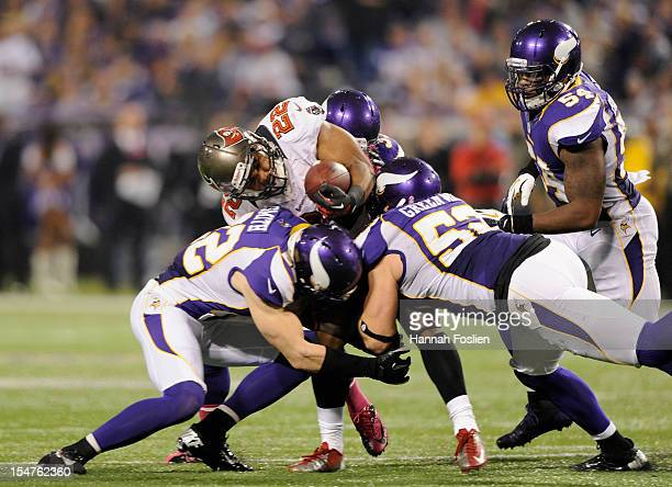 Doug Martin of the Tampa Bay Buccaneers is tackled by Harrison Smith Jamarca Sanford and Chad Greenway of the Minnesota Vikings as Jasper Brinkley...