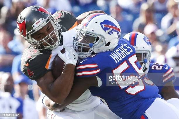 Doug Martin of the Tampa Bay Buccaneers is tackled by Jerry Hughes of the Buffalo Bills during an NFL game on October 22 2017 at New Era Field in...