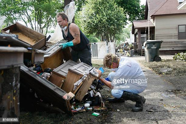 Doug McCoy helps Pam Zimmerman toss ruined furniture onto the curb as they clean up after the Iowa River inundated her house with flood waters June...