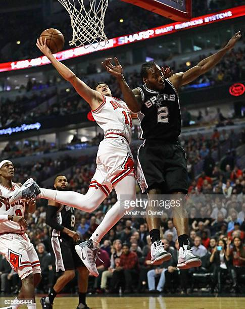 Doug McDermott of the Chicago Bulls puts up a shot against Kawhi Leonard of the San Antonio Spurs at the United Center on December 8 2016 in Chicago...