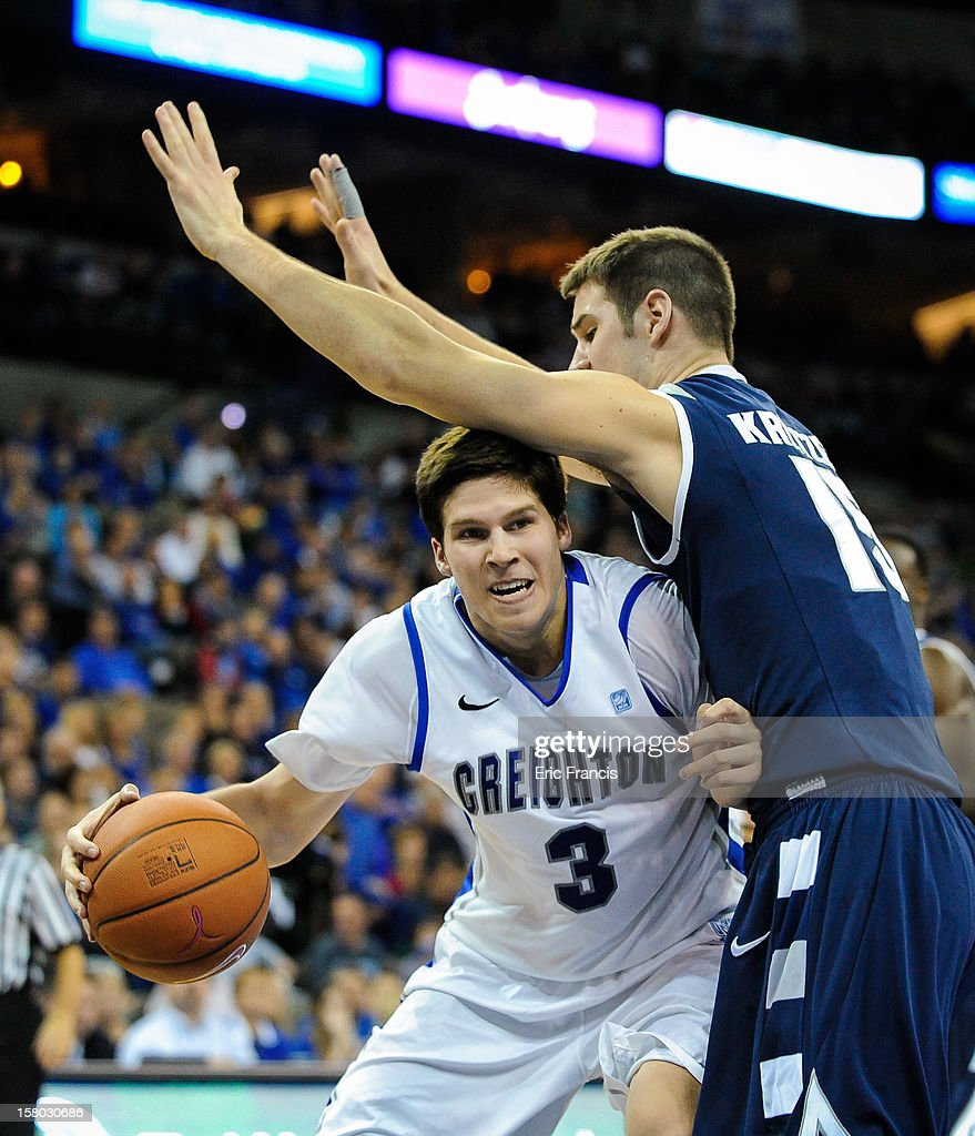 Doug McDermott #3 of the Creighton Bluejays drives into Jake Kretzer #15 of the Akron Zips during their game at the CenturyLink Center on December 9, 2012 in Omaha, Nebraska.