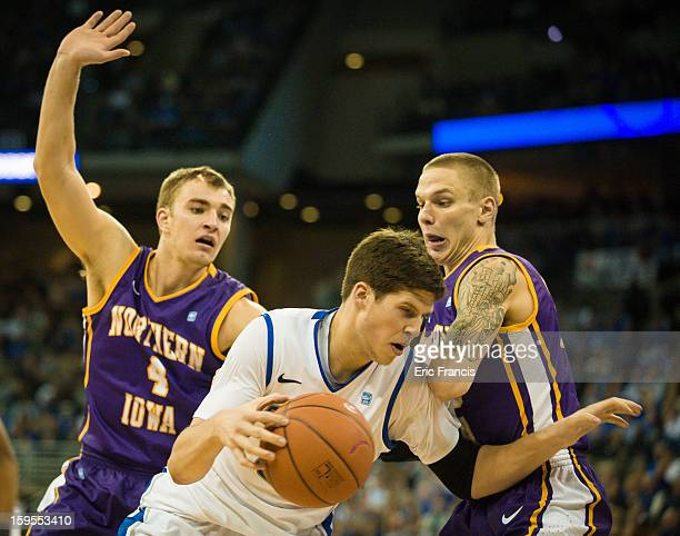 Doug McDermott of the Creighton Bluejays tries to work around Chip Rank and Marc Sonnen of the Northern Iowa Panthers during their game at the...