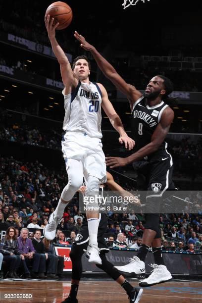 Doug McDermott of the Dallas Mavericks dunks against DeMarre Carroll of the Brooklyn Netson March 17 2018 at Barclays Center in Brooklyn New York...